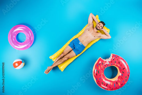 top view of handsome young man in shorts resting on inflatable mattress and smiling at camera on blue