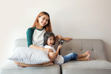 Asian kids using smartphone sitting together on sofa