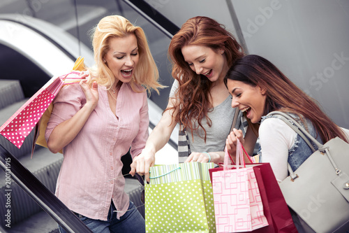 Sticker Young attractive girls with shopping bags in the city