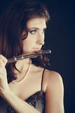 Woman playing transverse flute on black. - 200139918