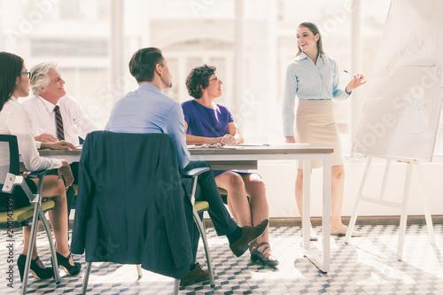 Ufny młody Kaukaski bizneswoman przedstawia jej pomysł koledzy. Wyjaśnia wykres na tablicy i przygląda się współpracownikom. Inni uważnie jej słuchali. Koncepcja szkolenia biznesowe
