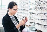 Woman taking glasses off shelf to try in optician shop - 200145777