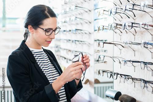 Kobieta bierze szkła z półki próbować w okulisty sklepie