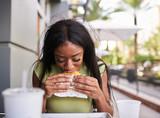 african american woman eating chicken sandwich