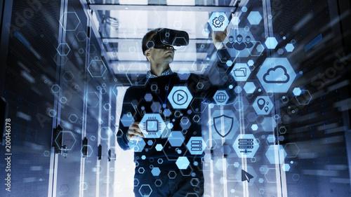 Inżynier informatyk noszący zestaw słuchawkowy Virtual Reality Współpracuje z oprogramowaniem Augmented Reality w Data Center. On Wirelessly wchodzi w interakcje z serwerami Rack dzięki wizualizacji ikon.