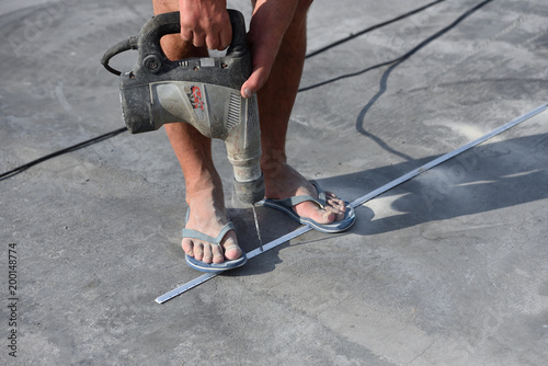 Męskie nogi w klapkach są bardzo zakurzone i brudne z powodu tego, że mężczyzna pracuje z dziurkaczem, wierci betonową podłogę