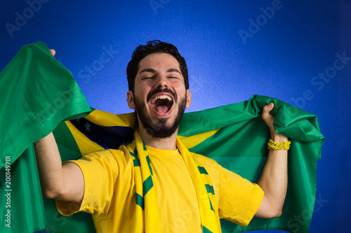 Supporter of National Team of football is holding the Brazil flag.