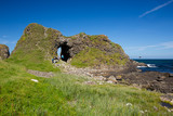 Irish landscape, green grass covered sea coast, with stone hill and cave, next to Ballintoy