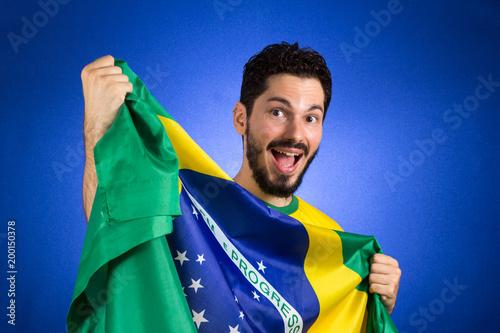Brazilian soccer football player holding Brazil flag.