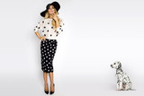 Beautiful, sexy blonde woman in elegant polka dots and a hat, standing on a white background next to a dalmatian dog