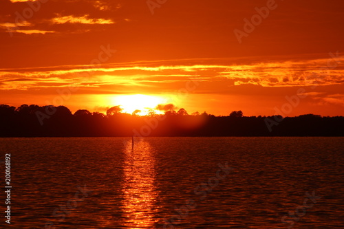 Fotobehang Rood traf. Vibrant dramatic orange sunset sky with cloudscape