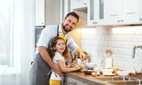 happy family in kitchen. Father and child daughter knead dough and bake biscuits . - 200173954