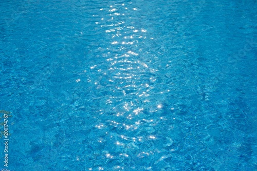 Foto Murales water ripples texture in swimming pool with sunny glare