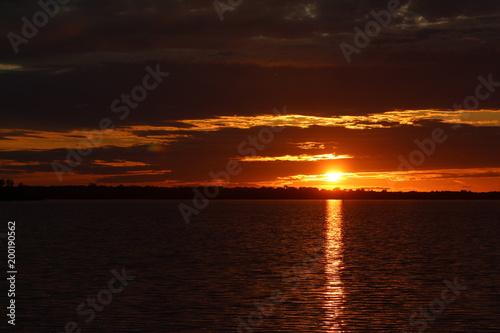 Foto op Plexiglas Bruin Sun setting behind dark clouds over the water with water reflection