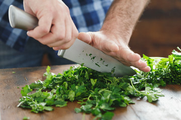 Close up male hands chopping fresh parsley © kucherav