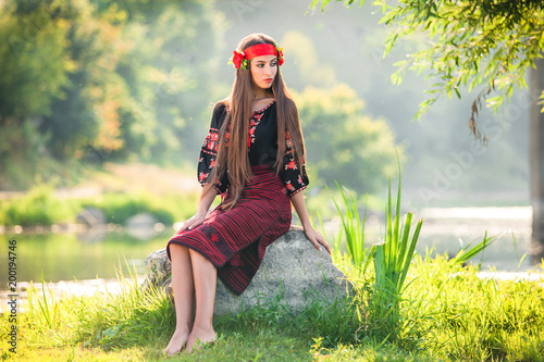 girl in a designer embroidered suit with patterns sits on the stone near the river