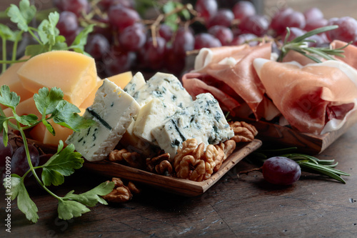 Various cheeses , grapes and prosciutto .