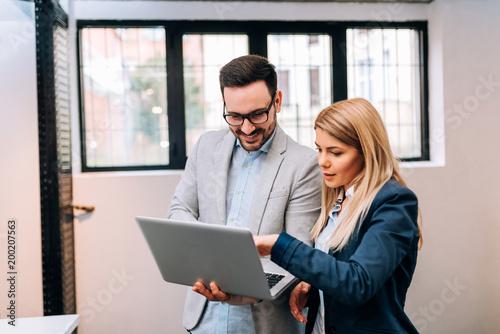 Młody biznesowy mężczyzna trzyma laptop podczas gdy dyskutujący nowego projekt z jego żeńskim kolegą