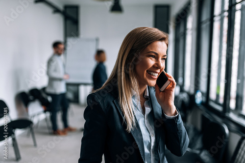 Portrait of a smiling blonde businesswoman talking on a phone during the break from a meeting. - 200207585