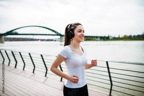 Smiling runner girl listening music.