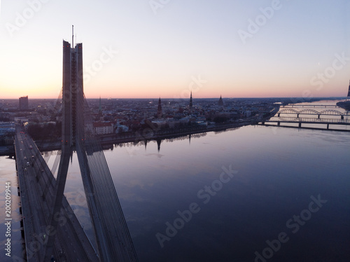 Aerial view on traffic bridge over river in sunrise, cars on bridge, city landscape view