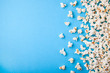 Popcorn scattered on blue background. Copy space for text