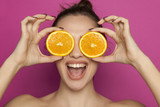 Happy young woman posing with slices of oranges on her face on pink background - 200220342