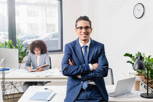 Smiling businessman standing in office with his female coworker by table with computer
