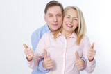 Happy middle aged couple in embraces and show thumb up. - 200228703