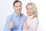 Happy middle aged couple in embraces and show thumb up. - 200228708