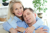 Close up photo of cheerful excited happy happily happy with toothy shining smile blond attractive woman and man, she is hugging him from the back and kisses - 200228968