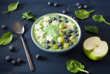 healthy green spinach smoothie bowl with blueberry, banana stars, kiwi, chia seed