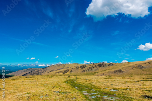 Foto op Aluminium Blauw Mountain landscape with clouds. Mountain valley road. The Altai mountains. Travel adventure vacation background