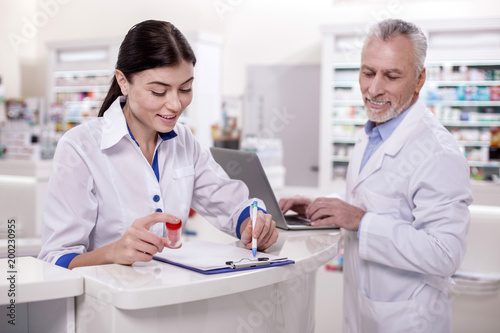Plexiglas Apotheek No experience. Positive female pharmacist taking notes while mature male doctor using laptop