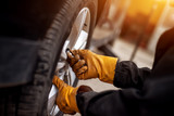 An experienced mechanic with orange gloves is putting screws on a placed wheel on a car. - 200235369