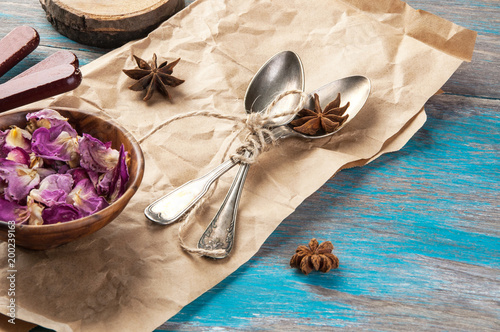 Vintage tea spoons and rose petals on wooden blue background