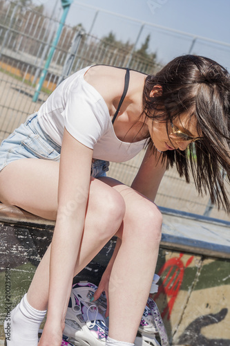 Teenage girl with long black hair wearing roller skates