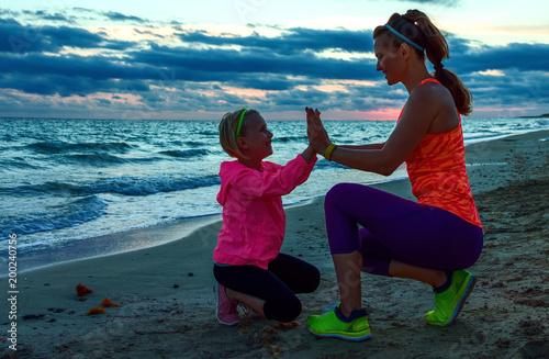młoda matka daje dziecko piątkę na wybrzeżu na zachód słońca