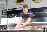food sale, small business and people concept - male seller with seafood at fish shop fridge