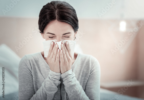 Foto Murales Home treatment. Ill exhausted unhappy woman sitting in the bright room holding a napkin and sneezing.