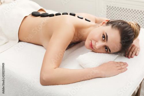 Kobieta coraz masaż gorącymi kamieniami w salonie spa