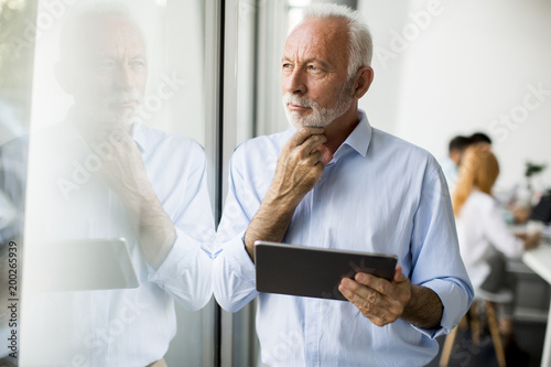 Foto Murales Senior businessman standing by window with digital tablet in his hand