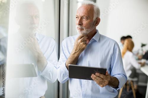 Starsza biznesmen pozycja okno z cyfrową pastylką w jego ręce