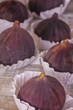 Figs fresh beautiful violet in paper shapes six pieces on a white wooden background, close-up