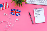 Learn new english vocabulary. Learn landuage concept. Computer keyboard, british and american flags, notebook for writing new vocabulary on pink background top view