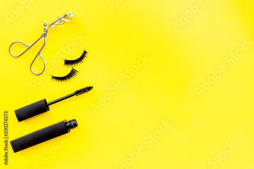 Makeup set for expressive eyelashes. Mascara, false eyelashes, eyelash curler on yellow background top view space for text - 200276373