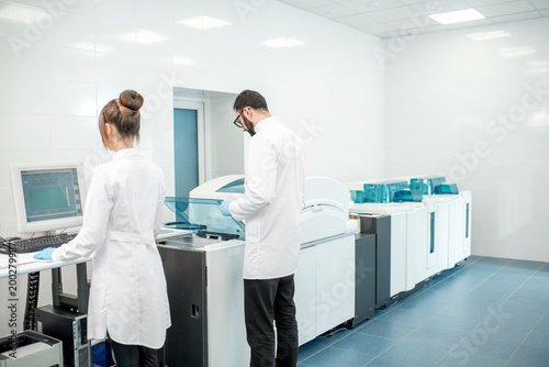 Foto Murales Couple of medics configuring analyzer machine in the modern laboratory
