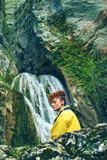 Mujer joven y pelirroja frente a una enorme cascada