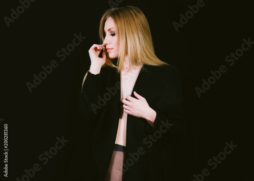 Sexy lady in nylons and long coat undressing, dark background. Elegant woman wearing black sensual lingerie. Erotic noir concept.  - 200281360