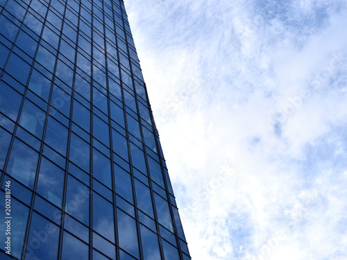 Wall of high modern business center building which reflects cloudy sky, location: Warsaw, Poland